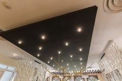 Beautifuul-Nahaufnahmeansicht von stilvollen modernen elektrischen Innendeckenleuchten auf schwarzer Platte Stockbilder