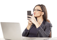 Beautifying in the office. Young businesswoman applying lip gloss at her workplace Stock Photo