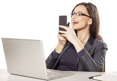 Beautifying in the office. Young businesswoman applying lip gloss at her workplace Royalty Free Stock Images