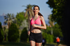 Beautiiul athletic runner in bright sportswear running in the park on trees background. Fitness and healthily lifestyle, sport and healthy concept, jogging and stock image