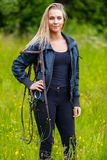 Beautilful young female horse rider standing in a green meadow royalty free stock photography