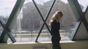 Beautisul blond flicka i svart som går vid fönstret och talar på telefonen arkivfilmer