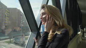 Beautisul blonde girl in black standing by the window and talking on the phone. Girl looks out the window, smiles and touches her hair. Sunlight falls on her stock footage
