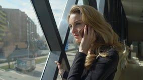 Beautisul blondynki dziewczyna w czarnym odprowadzeniu okno i opowiadać na telefonie zdjęcie royalty free