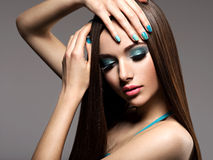 Beautiul elegant woman with turquoise make-up and nails. Straigh. Beautiul elegant woman with turquoise make-up and nails - pose at studio Stock Photo