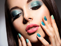 Beautiul fashion young adult girl with turquoise make-up and nai Stock Photo
