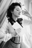 Beautiul female with parfum on window curtain. Black and white photography of beautiul female with parfum on window curtain light background Stock Images