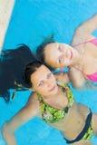 Beautiul girls in a pool. Two beautiul girls splashing around and enjoying the sun in a swimming pool Stock Photo