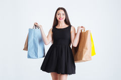 Beautiul happy woman standing with colorful shopping bags. Beautiul happy young woman in black dress standing with colorful shopping bags over white background Stock Photo