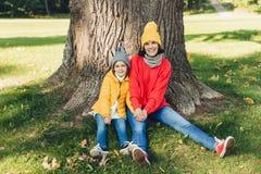Beautiul kobieta jest ubranym trykotowego kapelusz i swetaer siedzi wraz z jej małą córką blisko drzewa, odpoczynek outdoors w pi obrazy stock