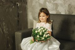 Beautiul little girl hold a bouquet of flowers at home. She sist on sofa at home and waiting for her mom. Bouquet of. Beautiul little girl hold a bouquet of royalty free stock images
