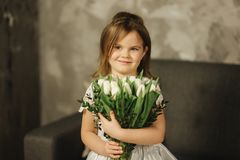 Beautiul little girl hold a bouquet of flowers at home. She sist on sofa at home and waiting for her mom. Bouquet of. Beautiul little girl hold a bouquet of stock image