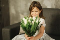 Beautiul little girl hold a bouquet of flowers at home. She sist on sofa at home and waiting for her mom. Bouquet of. Beautiul little girl hold a bouquet of stock photos
