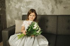 Beautiul little girl hold a bouquet of flowers at home. She sist on sofa at home and waiting for her mom. Bouquet of. Beautiul little girl hold a bouquet of stock photography