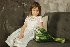 Beautiul little girl hold a bouquet of flowers at home. She sist on sofa at home and waiting for her mom. Bouquet of. Flowers on 8th of march. Present royalty free stock photo