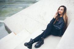 Beautuful smiley młoda kobieta siedzi na betonowych progach i opowiada telefonem Zdjęcia Stock