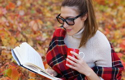 Beautuful woman reading a book. Beautiful woman with glasses and a warm scarf in a cage reading a book and drinking tea from a red cup in the  garden Stock Photos
