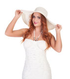 Beautuful woman with red long hair posing in white dress and hat Royalty Free Stock Image