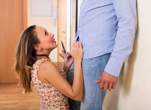 Beautuful woman unbuttons husband trousers Royalty Free Stock Photo