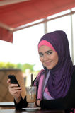 Beauty. Young muslim woman in head scarf using phone in cafe Royalty Free Stock Image