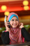 Beauty. Young muslim woman in head scarf using phone in cafe Royalty Free Stock Photos