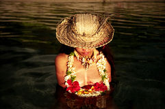 Beauty. A beautiful asian woman sitting in the polynesian waters in Tahiti, at sunset Stock Image