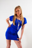 Beauty. Young female fashion model wearing a moden blue dress standing against a white back drop Stock Photos