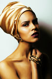 Beauty african woman in shawl on head, very elegant look with go. Ld jewelry close up mulatto makeup macro Royalty Free Stock Photos