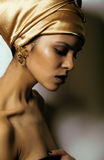 Beauty african woman in shawl on head, very elegant look with gold jewelry. Close up Royalty Free Stock Images