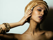 Beauty african woman in shawl on head, very elegant look with gold jewelry. Close up Stock Image