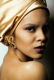 Beauty african woman in shawl on head, very elegant look with gold jewelry. Close up Royalty Free Stock Photo
