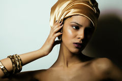 Beauty african woman in shawl on head, very. Elegant look with gold jewelry close up Royalty Free Stock Photos