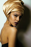 Beauty african woman in shawl on head, very. Elegant look with gold jewelry close up Stock Images