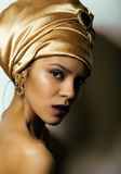 Beauty african woman in shawl on head, very. Elegant look with gold jewelry close up Stock Photography