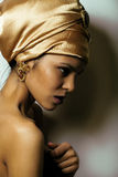 Beauty african woman in shawl on head, very. Elegant look with gold jewelry close up mulatto makeup Royalty Free Stock Photos