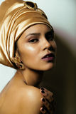 Beauty african woman in shawl on head, very. Elegant look with gold jewelry close up mulatto makeup Stock Photography