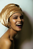 Beauty african woman in shawl on head. Very elegant look with gold jewelry close up smiling Stock Images