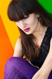 Beauty against rainbow. Bright colorful portrait of young brunette female model with bright purple lips wearing black lace top and violet skirt against rainbow Royalty Free Stock Photos