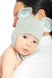 Beauty amazed newborn baby boy. Beauty newborn baby with knitted mouse cap standing on his mother shoulder isolated on white background Stock Image