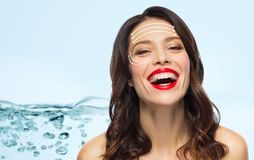 Beautiful laughing woman with face lifting arrows. Beauty and anti-age concept - happy laughing young woman with face lifting arrows over blue background with royalty free stock photos