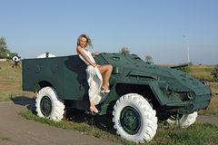 Beauty and the armored car. A young woman near sarogo armored car Royalty Free Stock Images
