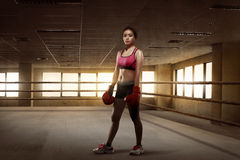 Beauty asian girl boxer with red gloves standing in the boxing r Stock Photos