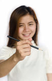 Beauty Asian Girl holding a black Pencil . Royalty Free Stock Image