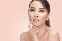 Beauty Asian Portrait. Beautiful Woman Touching her Lips. Perfect Fresh Skin. Pure Beauty Model. Youth and Skin Care Concept. .on pink background with clipping Stock Images