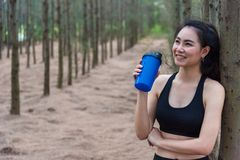 Beauty Asian sport woman resting and holding drinking water bottle and relaxing in middle of forest after tired from jogging. stock images