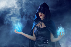 Beauty asian witch woman. Asian beauty witch woman with blue fire on her hand, dark background with fog covered Stock Photography