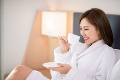 Woman enjoy coffee in morning. Beauty asian woman drink coffee and enjoy a wonderful morning in the hotel royalty free stock photos