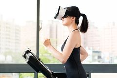Beauty asian woman running treadmill by VR headset glasses Royalty Free Stock Image