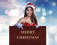 Beauty asian woman in santa dress pointing Merry Christmas text Stock Photography