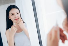 Beauty Asian Woman use Acne Gel Skincare after Cleansing on Face stock photography